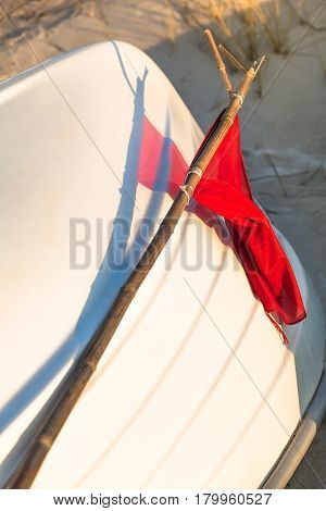 Closeup of translucent red signal flag and play of colors with bamboo pole on white rowboat upside down at the beach (copy space)