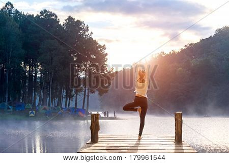 Healthy woman practicing yoga on the bridge in the nature