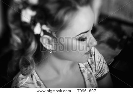 Beautiful bride putting on floral head wreath stylist doing hairstyle for blonde woman in stylish robe morning wedding preparation face closeup