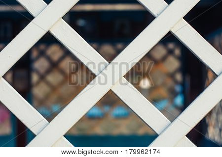 Chain link fencing behind a wooden lattice.