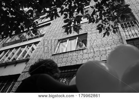 gorgeous bride smiling and looking from window in building to bridesmaids with balloons in the morning. getting ready for wedding ceremony. happy stylish woman. black white photo
