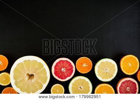 Frame of lemon, orange, mandarin, grapefruit and sweetie on black background. Flat lay, top view.