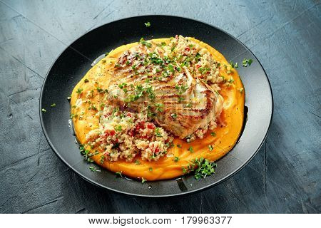 Soy-glazed cod loin fillet with cous-cous salad on butternut squash puree.
