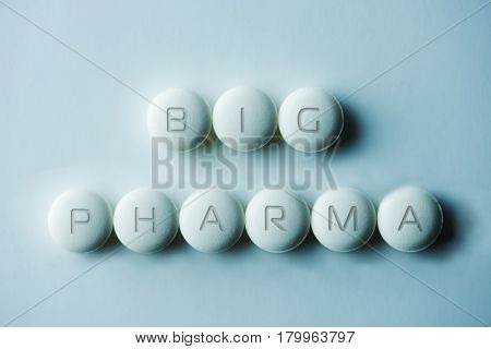 Big Pharma.?Tablets or pills, laid on white background with the letters BIG PHARMA. Intentionally shot in low key and surreal bluish tone.
