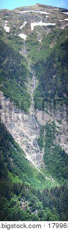 The vertical panoramic view of Juneau mountain waterfall in Juneau city (Alaska).