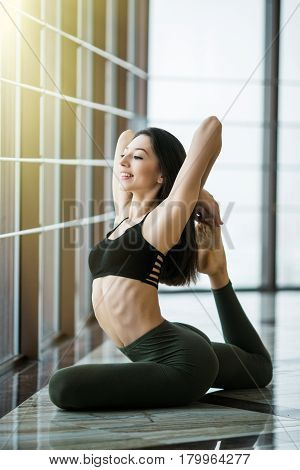 Young Slim Blond Woman In Yoga Class Making Beautiful Asana Exercises. Girl Do Mermaid Pose, Variati