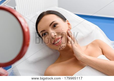 Beaming lady with perforation lines looking at mirror. She leaning in bed in surgical room