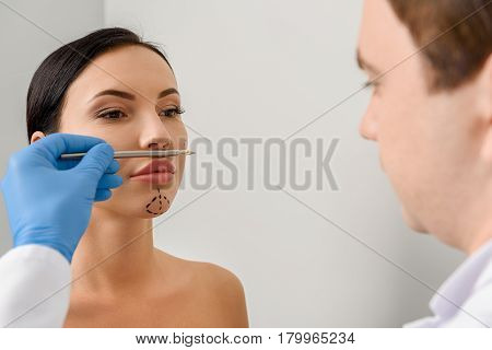 Unconcerned woman with perforation lines looking at physician. Doctor marking where correlating face
