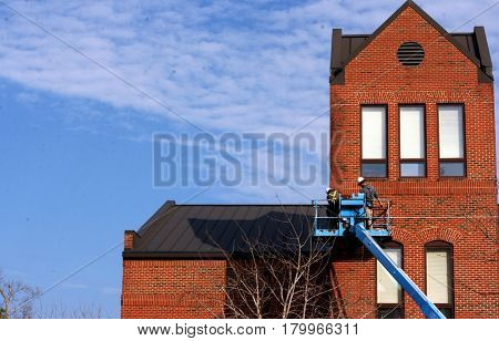 Two working men on a blue scaffold working on a commercial brick building