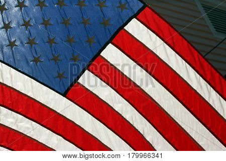 A part of a red, white, and blue American Flag with stripes and stars forever