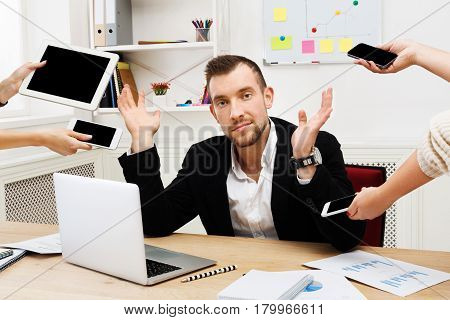 Tired from multitasking. Frustrated businessman workaholic sitting at workplace in modern office