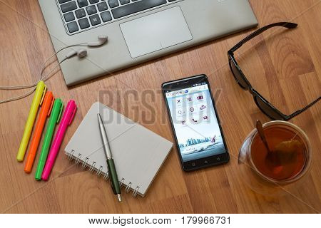 Nitra, Slovakia, april 3, 2017: Qatar airways application in a mobile phone screen. Workplace with a laptop, an earphones, notepad, pen, tea, sunglasses and color markers on wooden background