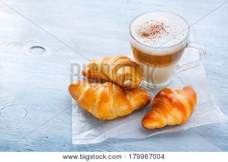 Breakfast with Latte macchiato coffee and croissants. Selective focus