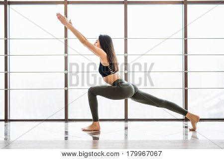 Virabhadrasana Beautiful Yoga Woman Practice Near Window Yoga Room Studio Background. Yoga Concept.