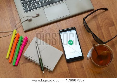 Nitra, Slovakia, april 3, 2017: Google hangouts application in a mobile phone screen. Workplace with a laptop, an earphones, notepad, pen, tea, sunglasses and color markers on wooden background