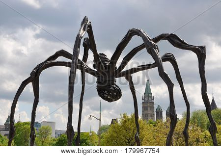 OTTAWA, CANADA - MAY 15, 2012: Sculpture Maman and Parliament Buildings in Ottawa, Ontario, Canada.