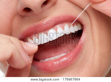 woman smile with tooth floss