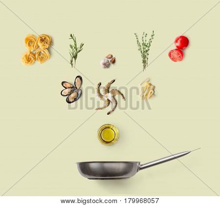 Cooking italian food, seafood pasta, isolated on yellow background. Frutti di mare with fettuccine spaghetti. Mussels, prawn, shrimp, calamari rings and other ingredients over frying pan