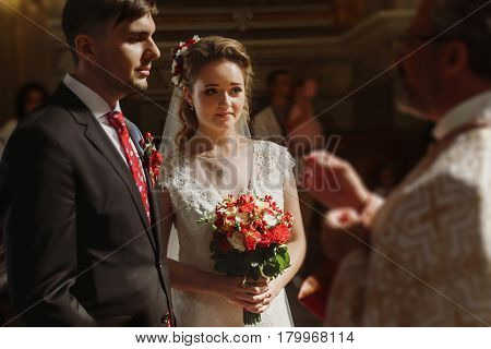 Beautiful bride and handsome groom kissing wedding rings spiritual christian couple kissing gold rings during wedding ceremony in church romantic moment