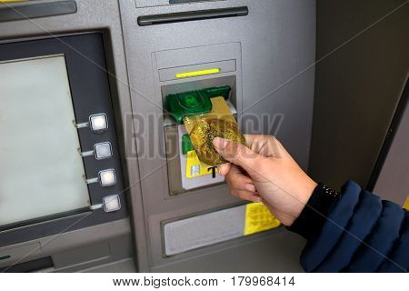 Female hand inserts ATM. Cash withdrawals from ATMs