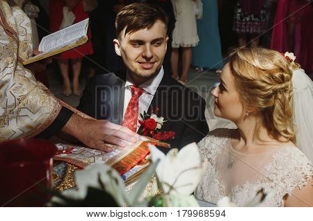 Happy emotional bride and groom give vows during wedding ceremony in church handsome groom and bride taking vow on bible near christian priest faces closeup