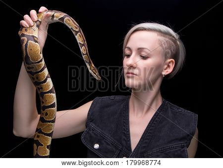 Portrait of blond woman with snake on black background