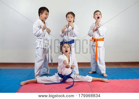 Four children demonstrate martial arts working together. Fighting position active lifestyle practicing fighting techniques