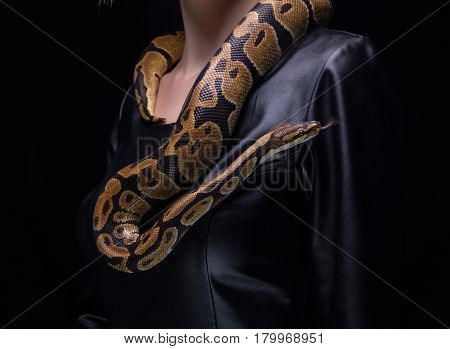 Woman and ball python on black background