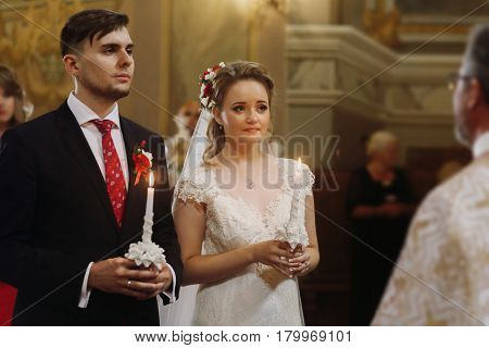 Spiritual couple bride and groom holding candles during wedding ceremony in christian church emotional moment during ceremony for man and woman