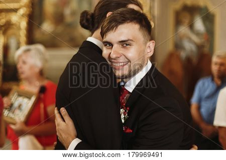 Happy smiling groom hugging bestman after wedding ceremony in church stylish handsome man embracing groomsman friend indoors and smiling