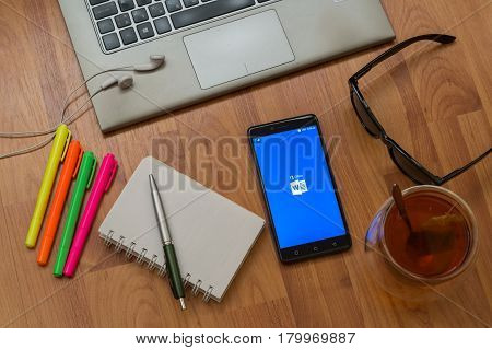 Nitra, Slovakia, april 3, 2017: Microsoft office word application in a mobile phone screen. Workplace with a laptop, an earphones, notepad, pen, tea, sunglasses and color markers on wooden background