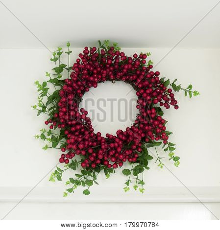 Wreath of green leaves and red berries over the entrance door