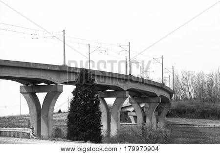 A curving concrete overpass bridge with cement pillars in black and white
