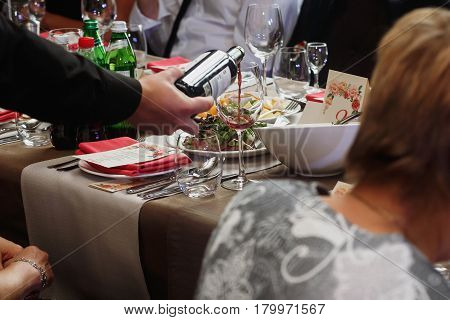 Waiter Pouring Wine In Glass Of Guest At Luxury Stylish Decorated Table With Food At Wedding Recepti