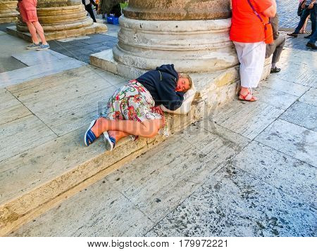 Rome, Italy - September 10, 2015: A homeless woman sleeping lying in a street in the center of Rome, Italy on September 10, 2015