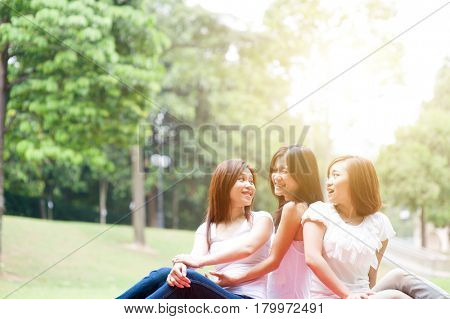 Group of Asian women having fun at outdoor park, sisters or girlfriends, friendship concept, sun flare background.