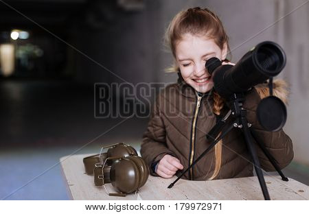 So curious. Positive cheerful pretty girl standing near the telescope and looking into it while smiling