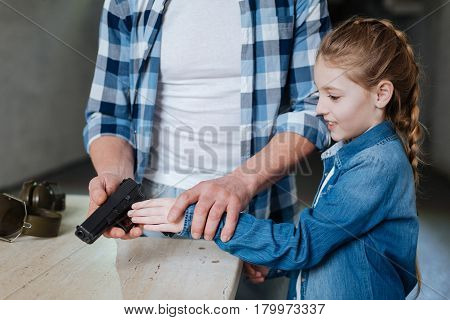 Is it dangerous. Pretty exited cute girl standing near her father and taking a gun while learning how to shoot