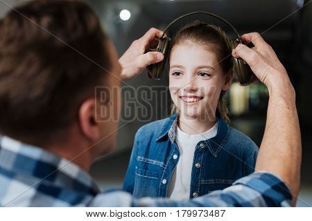 Father and daughter. Cute happy positive girl looking at her father and smiling while preparing to shoot