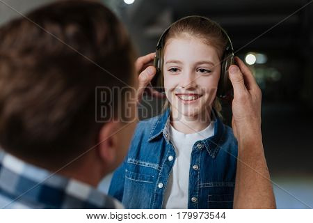Shooting lesson. Delighted positive nice girl wearing headphones and looking at her father while getting ready for the shooting lesson