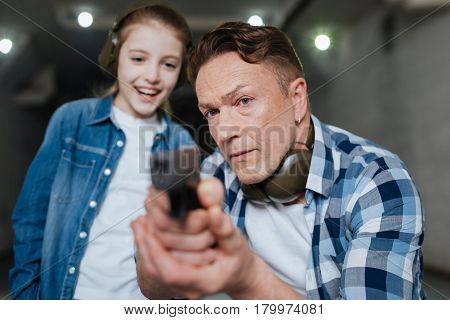 Self protection training. Serious handsome nice man holding a gun and aiming while teaching his daughter to defend herself