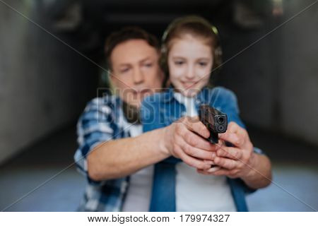 Shooting with a gun. Joyful smiling delighted girl holding a handgun and shooting while enjoying her time in the shooting gallery