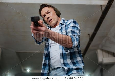 Using a handgun. Determined serious professional marksman looking at his aim and holding a handgun while directing it
