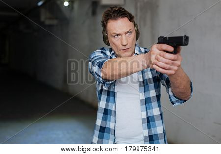 Professional marksman. Handsome nice professional marksman wearing headphones and holding a handgun while aiming at the target