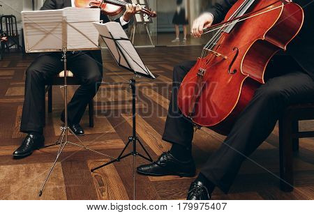 Elegant string quartet performing at wedding reception in restaurant handsome man in suits playing violin and cello at theatre play orchestra close-up music concept