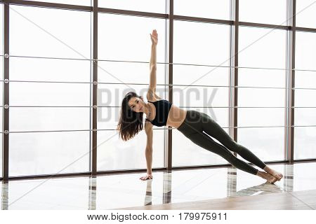 Side Plank. Beautiful Yoga Woman Practice Near Window Yoga Room Studio Background. Yoga Concept.