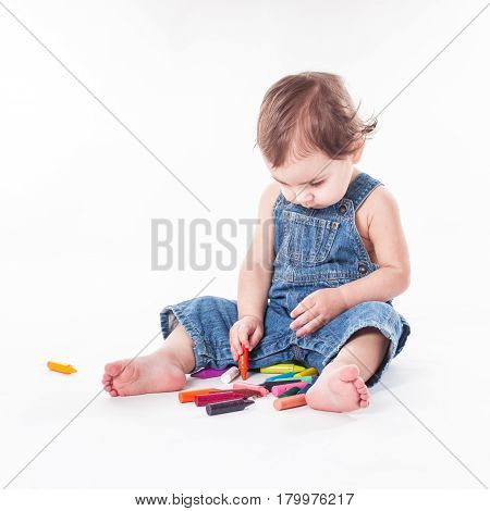 Baby girl is writting something on the big paper, sitting on it