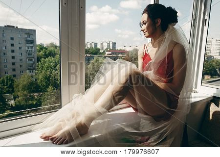 Beautiful Brunette Bride In Sexy Red Robe With White Veil Posing, Looking Out The Window, Morning Pr