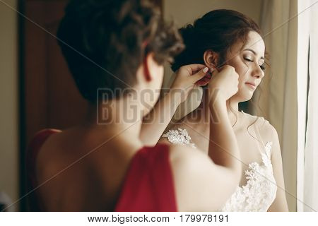 Beautiful Bridesmaid Helping Brunette Bride In White Wedding Dress Put On Luxury Earrings, Morning W