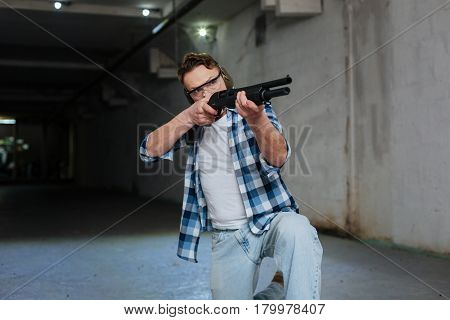 Position for shooting. Confident skilled nice shooter wearing protective glasses and sitting on one knee while shooting with a rifle